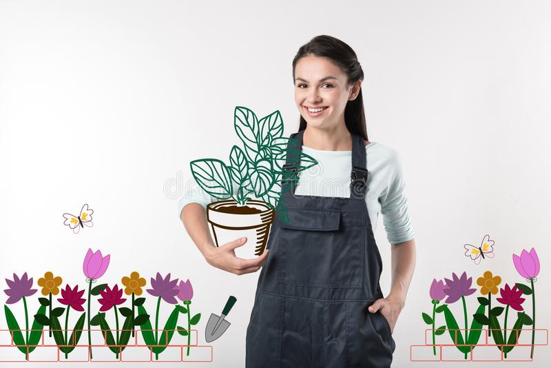Positieve tuinman die blij terwijl het houden van een grote installatie kijken royalty-vrije stock afbeelding