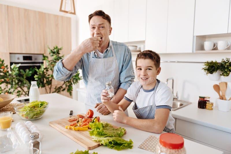 Positieve vader en zijn kleine zoon die cookign samen van genieten royalty-vrije stock afbeeldingen