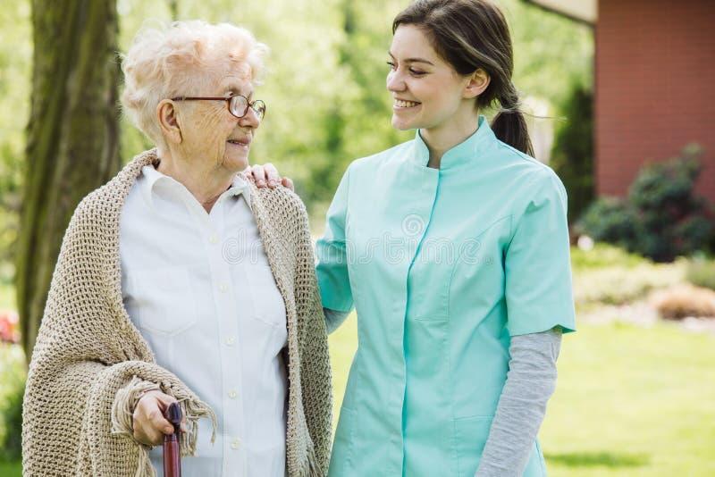 Positieve verzorger en oudere vrouw in de tuin stock foto's