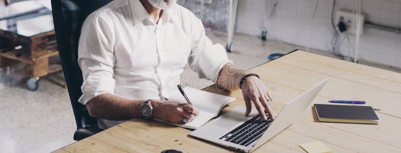 Positieve Volwassen zakenman die mobiele laptop computer met behulp van terwijl het zitten bij houten lijst op moderne coworking  royalty-vrije stock fotografie