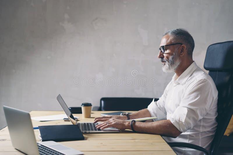 Positieve Volwassen zakenman die mobiele laptop computer met behulp van terwijl het zitten bij houten lijst op moderne coworking  stock afbeeldingen