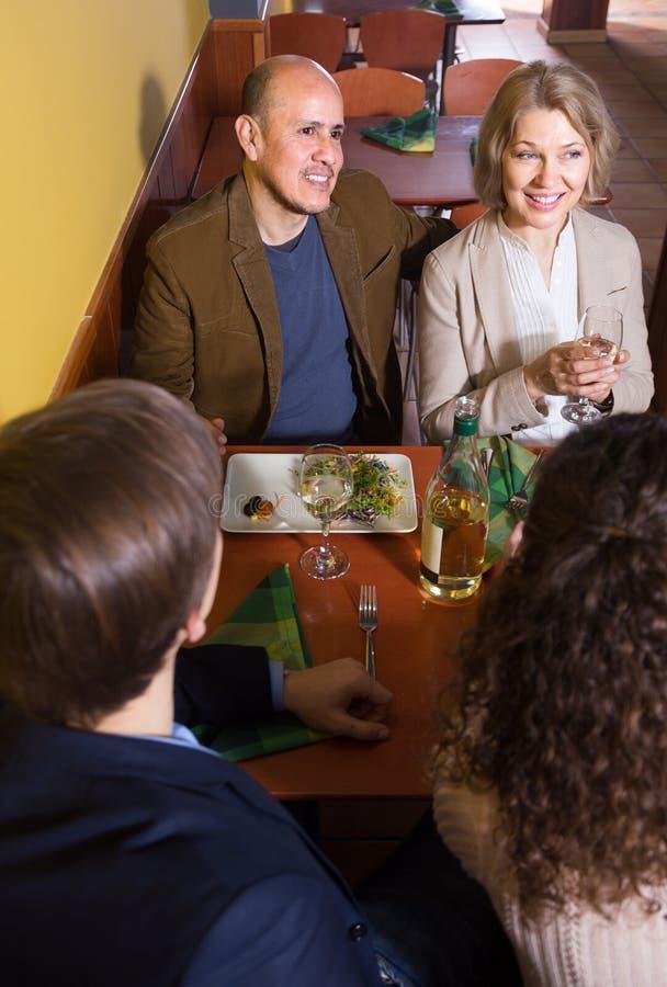 Positieve volwassenen die met wijn en diner in restaurant lachen royalty-vrije stock foto's