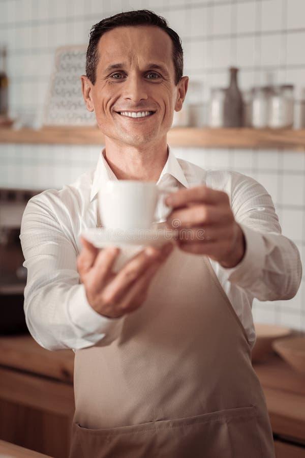 Positieve vriendschappelijke barista die u koffie geven stock afbeelding