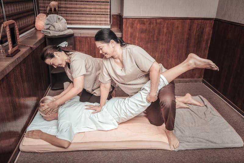 Positieve vrolijke Aziatische vrouwen die in paar werken stock afbeeldingen