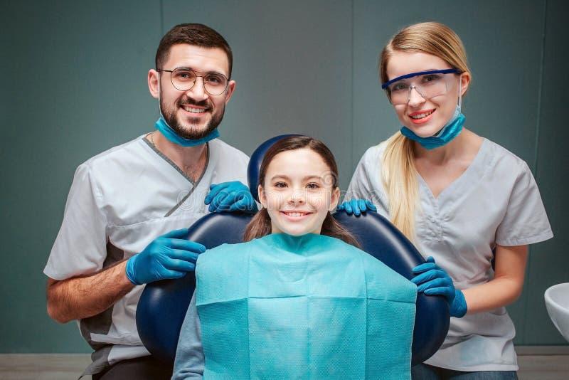 Positieve vrolijke mannelijke en vrouwelijke tandarts met meisjespatiënt Zij kijken recht samen en glimlach De volwassenen houden royalty-vrije stock foto