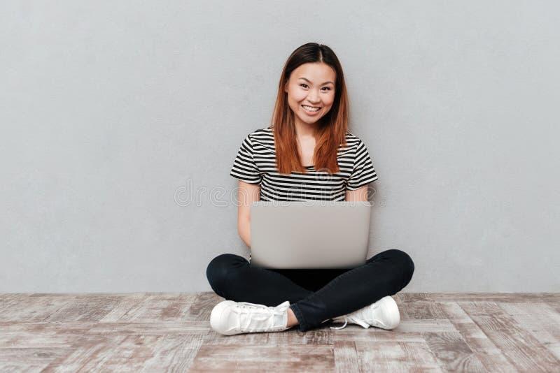 Positieve vrolijke vrouwenzitting op vloer met laptop stock afbeelding