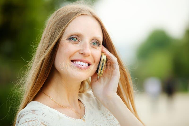 Positieve vrouw die door mobiel roepen royalty-vrije stock afbeeldingen