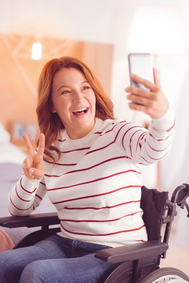 Positieve vrouw die selfies in de rolstoel maken royalty-vrije stock foto