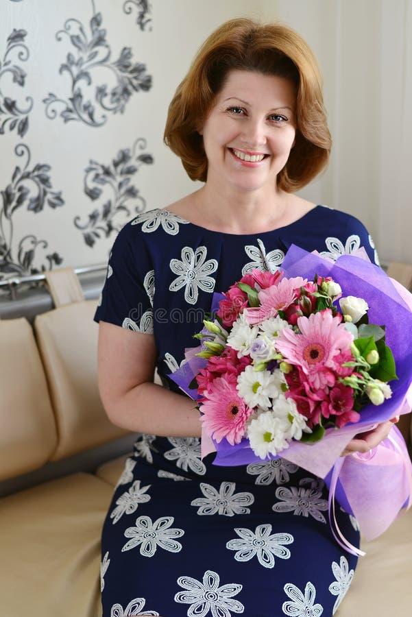 Positieve Vrouw met een boeket van bloemen in de ruimte stock fotografie