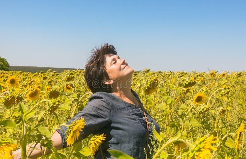 Positieve vrouw onder gebied van zonnebloemen stock foto