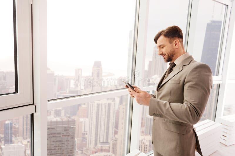 Positieve zakenman die zich in het bureau dichtbij venster bevinden royalty-vrije stock foto