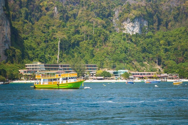 Positif, color? au bateau touristique de vitesse de passager vert et jaune, croisant pr?s de la plage railay photo libre de droits
