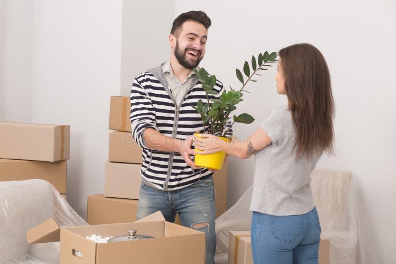 Position à la maison mobile de jeunes couples enthousiastes étroite ainsi que des usines dans leurs mains images libres de droits