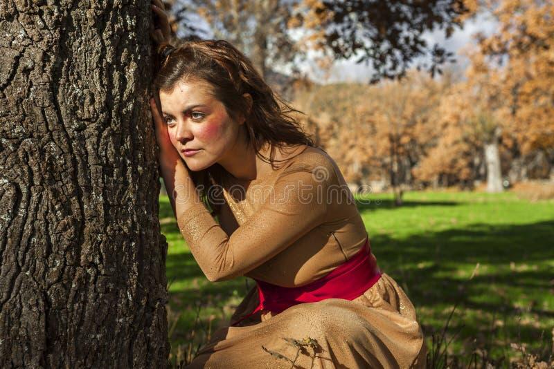 Position élégante tirée moyenne de jeune femme de portrait dans un arbre Regard à l'extérieur Automne de coucher du soleil image stock