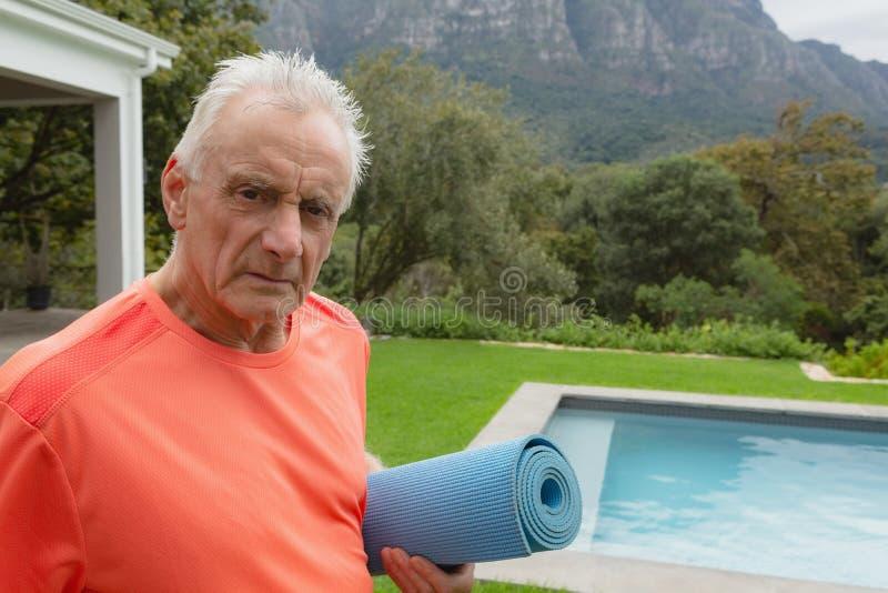 Position active d'homme supérieur avec le tapis d'exercice près du poolside dans l'arrière-cour images stock