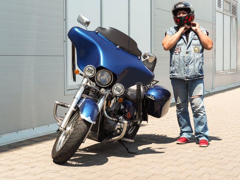 Position adulte de motard à côté de moto photographie stock