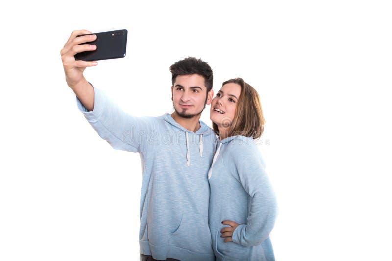 Position affectueuse de couples d'isolement sur le blanc et faisante le selfie utilisant le téléphone portable photographie stock libre de droits