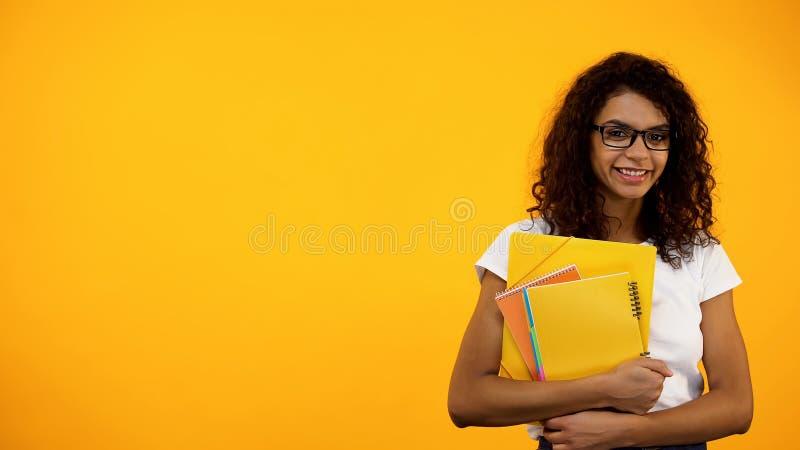 Position afro-am?ricaine de sourire d'?tudiant avec des livres, programmes d'enseignement photographie stock