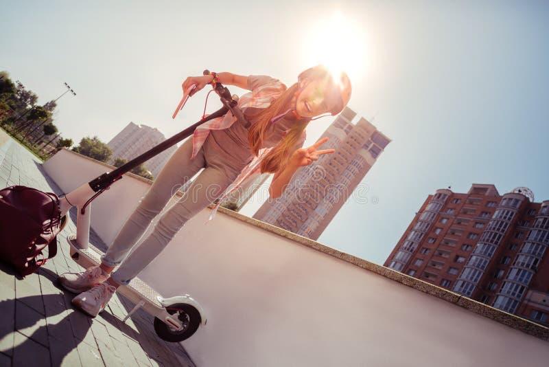 Position aimable de fille près de son électro cycle photo stock