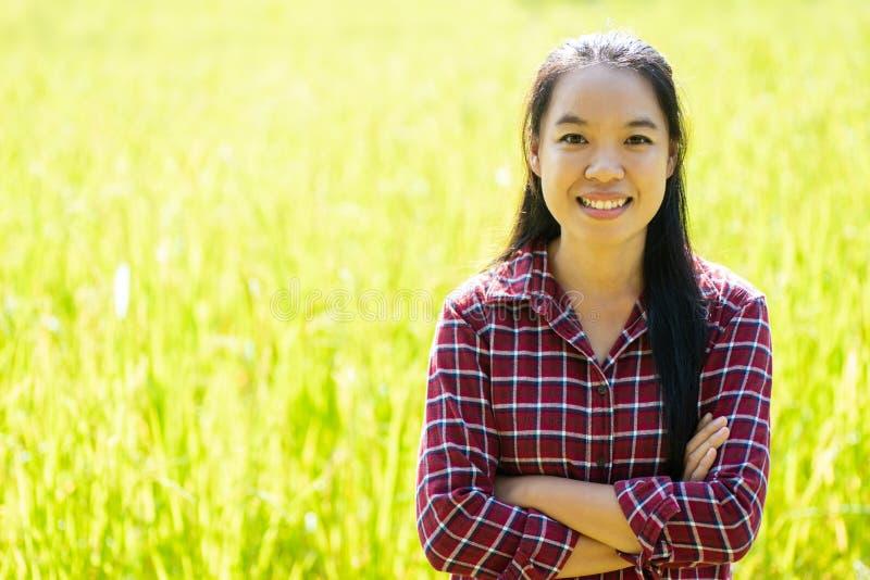 Position asiatique d'agriculteur de jeune femme dans le domaine organique de riz photos stock