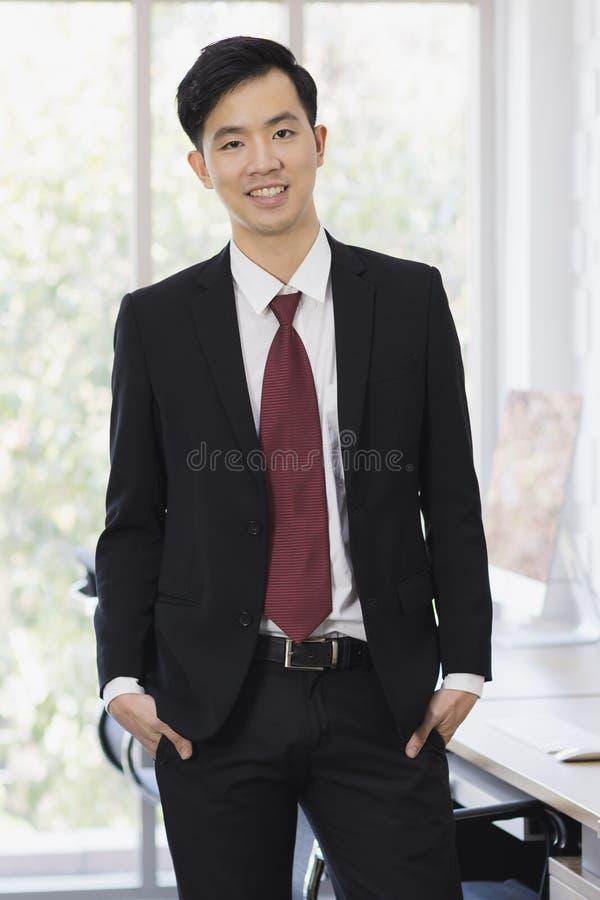 Position asiatique d'homme d'affaires et pose dans le bureau photographie stock