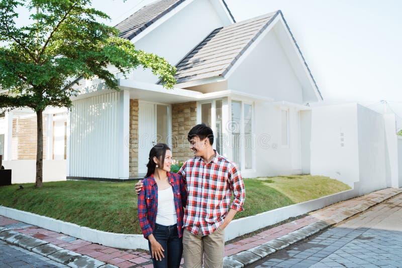 Position asiatique de couples devant leur nouvelle maison photos libres de droits