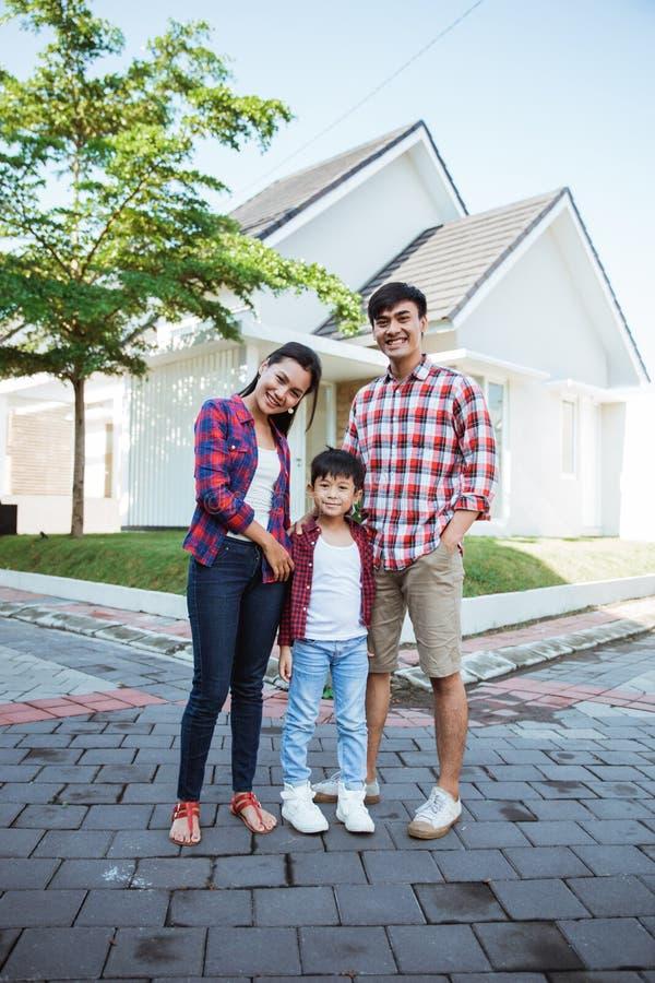 Position asiatique de famille devant leur nouvelle maison ensemble images stock