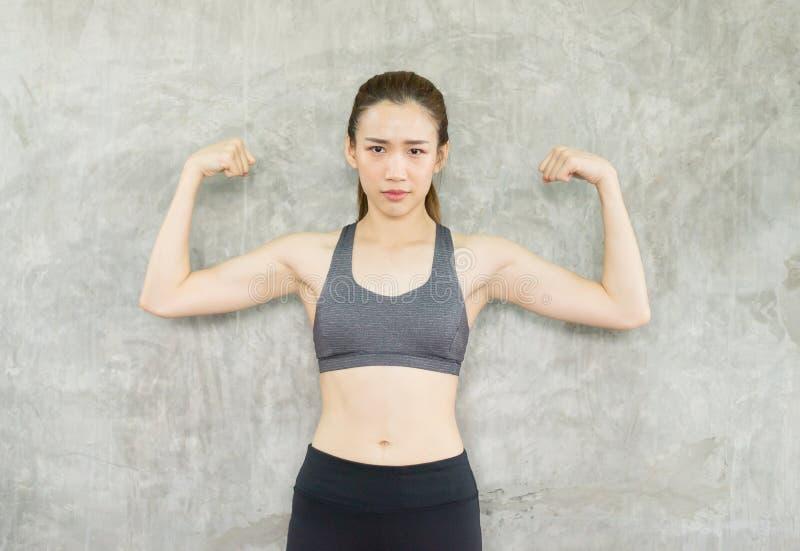 Position asiatique forte de posture de femme et levage vers le haut de ses bras et muscle d'exercices au gymnase image libre de droits