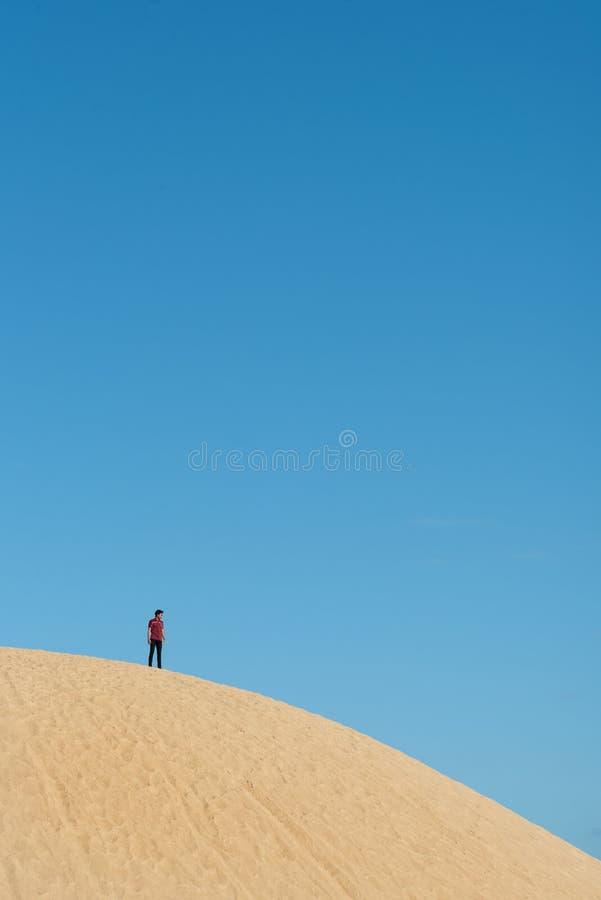 Position asiatique masculine seulement jeune sur la dune de sable photos stock