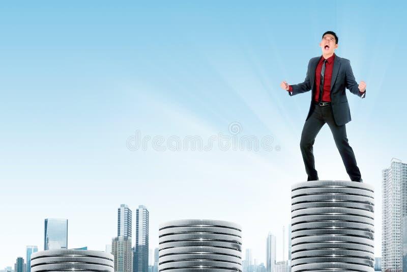 Position asiatique réussie d'homme d'affaires sur les plus hautes pièces en argent photographie stock libre de droits