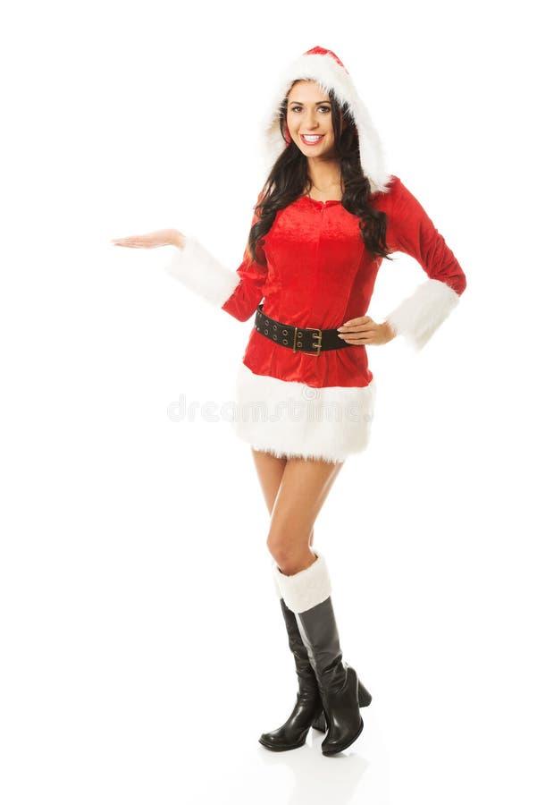 Position attrayante de femme de Santa, participation quelque chose invisible sur la main droite photos stock