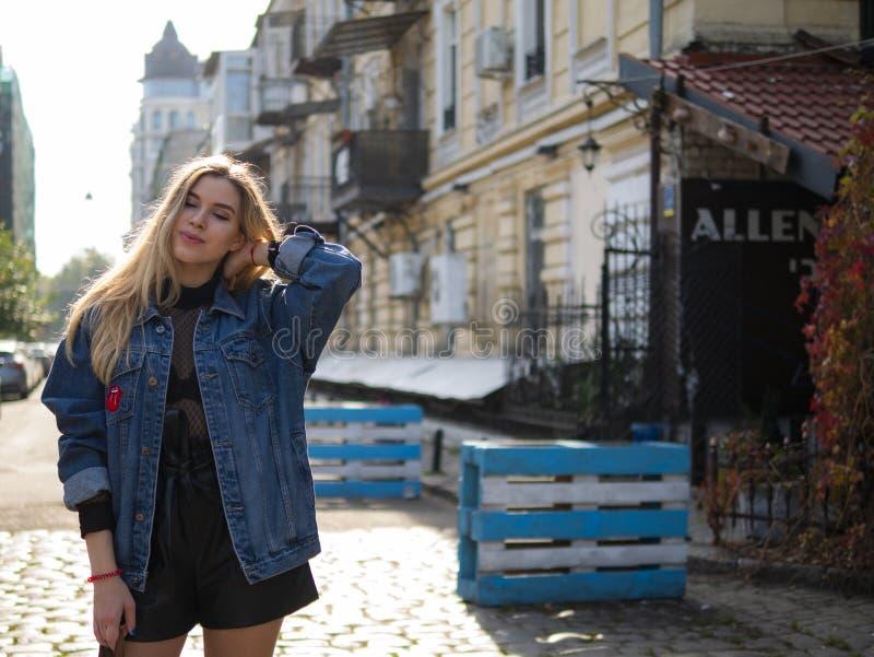 Position attrayante de fille sur la rue avec ses cheveux dans une veste de denim contre le contexte d'un bâtiment moderne photos stock