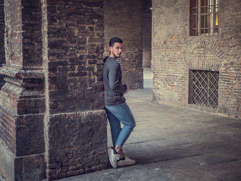 Position attrayante de jeune homme contre le vieux mur de briques image libre de droits