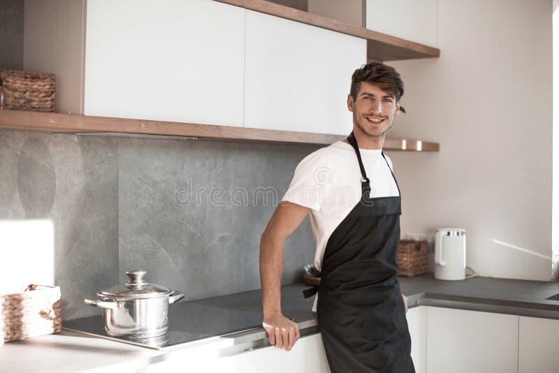 Position attrayante de jeune homme près de la table de cuisine photo libre de droits