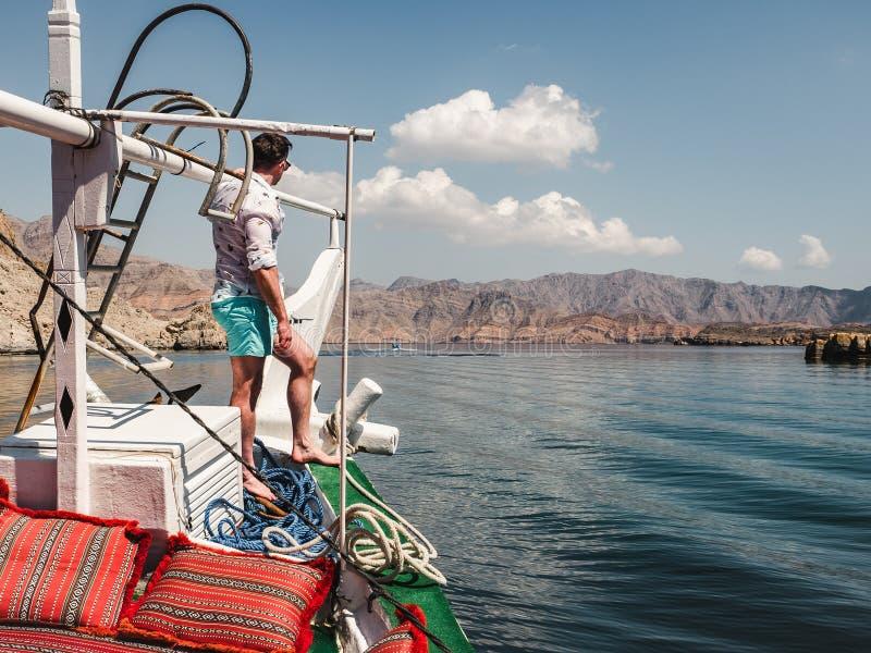 Position attrayante et à la mode d'homme sur un bateau photographie stock libre de droits
