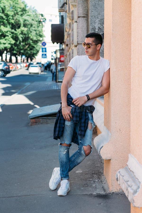 Position attrayante et sexy de type sur la rue dans des lunettes de soleil confiance en soi, flatulence et arrogance mod?le, posa photo libre de droits