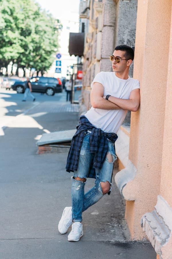 Position attrayante et sexy de type sur la rue dans des lunettes de soleil confiance en soi, flatulence et arrogance mod?le, posa photos libres de droits