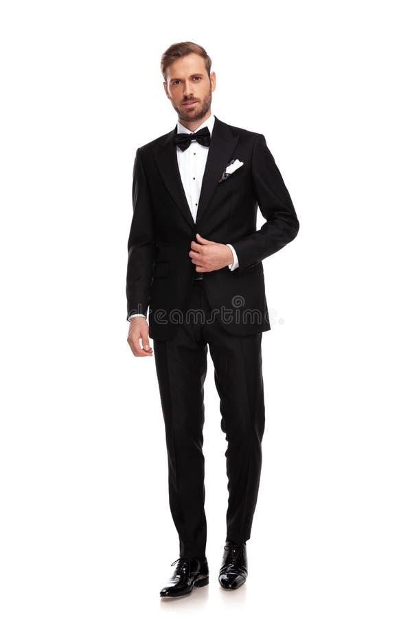 Position belle d'homme d'affaires et boutonnage du costume noir photo stock