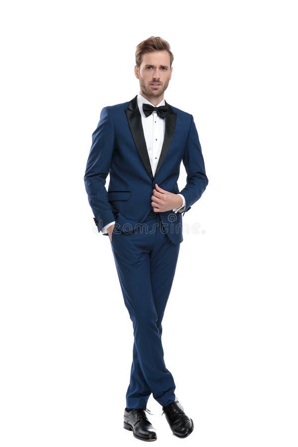 Position belle de type avec des jambes croisées et boutonnantes sa veste image stock