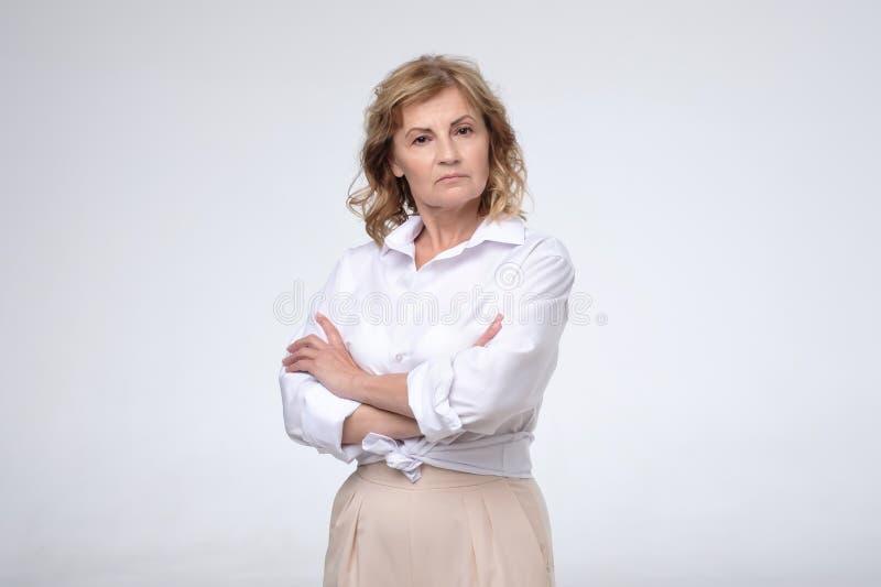 Position blanche de port de chemise de femme mûre avec les bras pliés regardant la caméra photographie stock