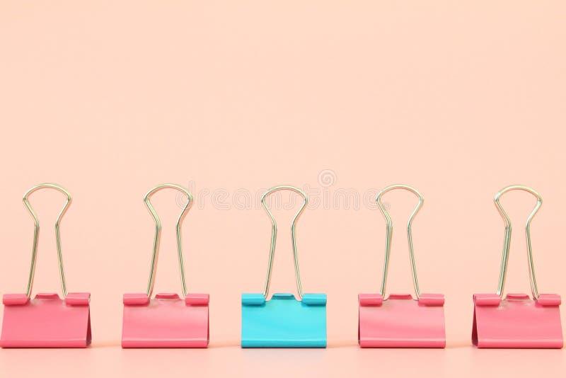 Position bleue d'agrafe de reliure hors des agrafes roses de reliure sur le fond orange avec l'espace de copie pour s'ajouter ou  photographie stock