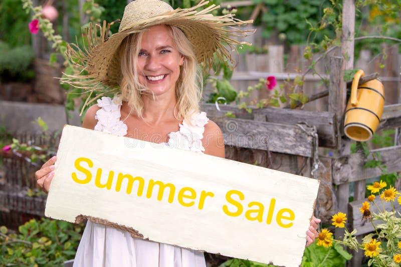 Position blonde de femme dans le jardin et signe de se tenir avec la vente d'été de mot photo libre de droits