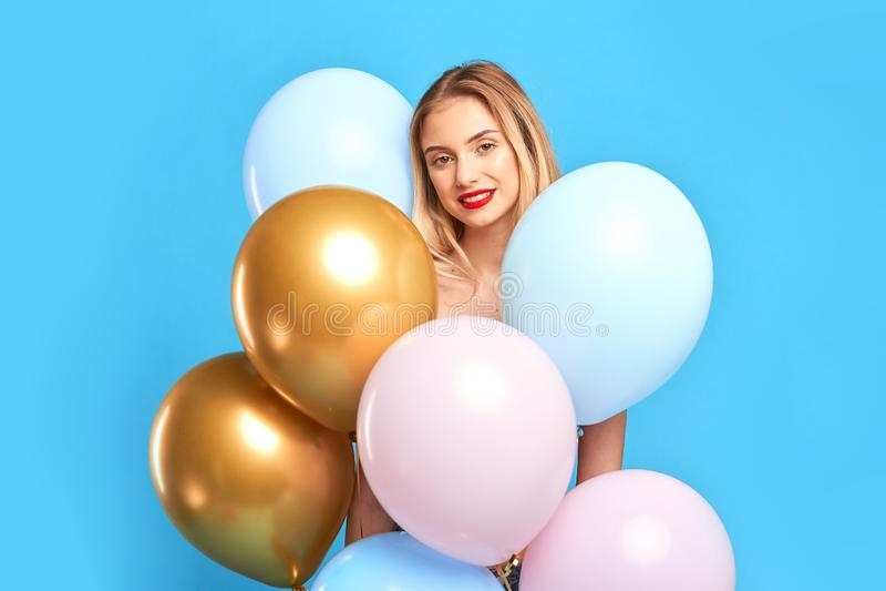 Position blonde de sourire de fille derrière beaucoup de ballons à air images libres de droits