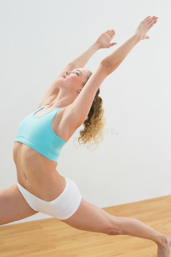 Position blonde mince focalisée dans la pose élevée de mouvement brusque photo stock