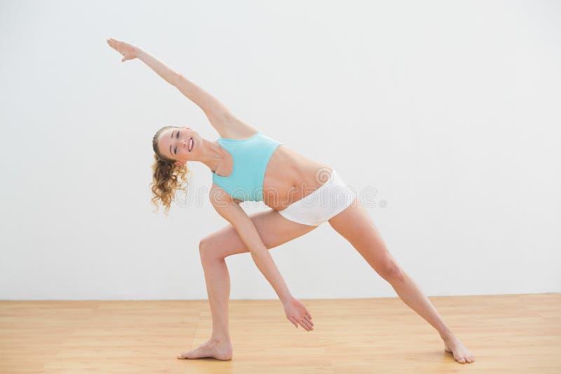 Position blonde mince heureuse dans la pose prolongée d'angle latéral image stock