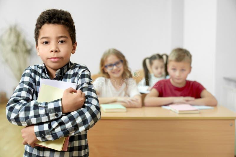 Position d'écolier dans la salle de classe, tenant des livres, posant photographie stock