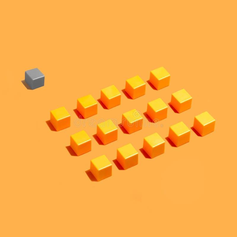 Position d'étranger : rangées des cubes identiques jaunes et derrière le gra photographie stock