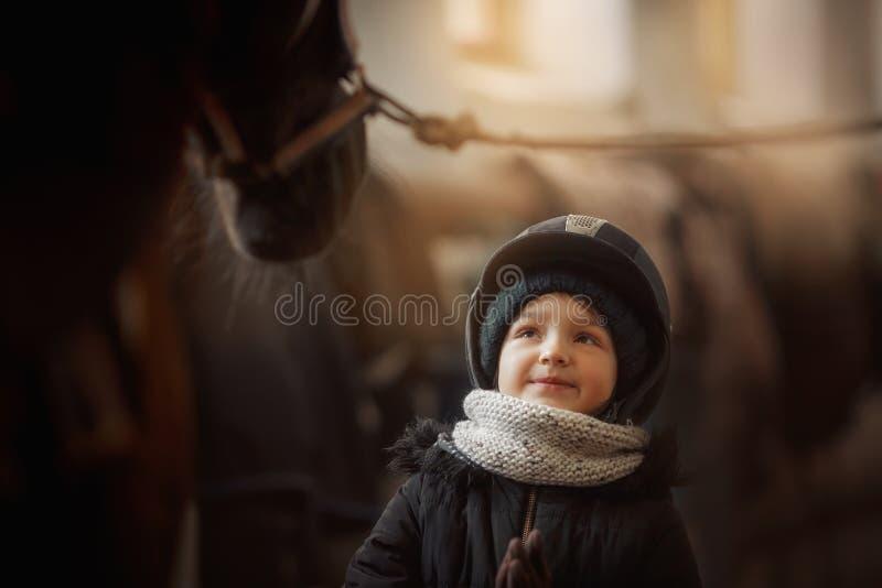 Position d'adolescente avec le cheval dans une ?curie images stock