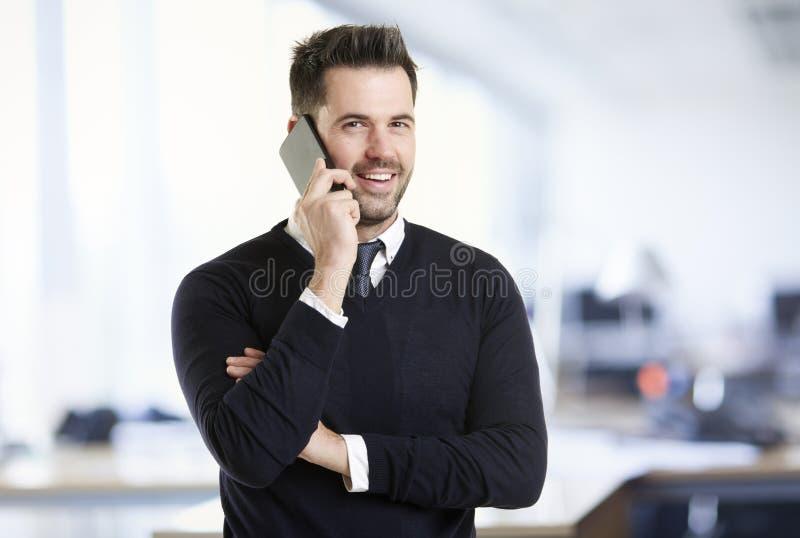 Position d'homme d'affaires dans le bureau et parler avec quelqu'un à son téléphone portable photographie stock libre de droits