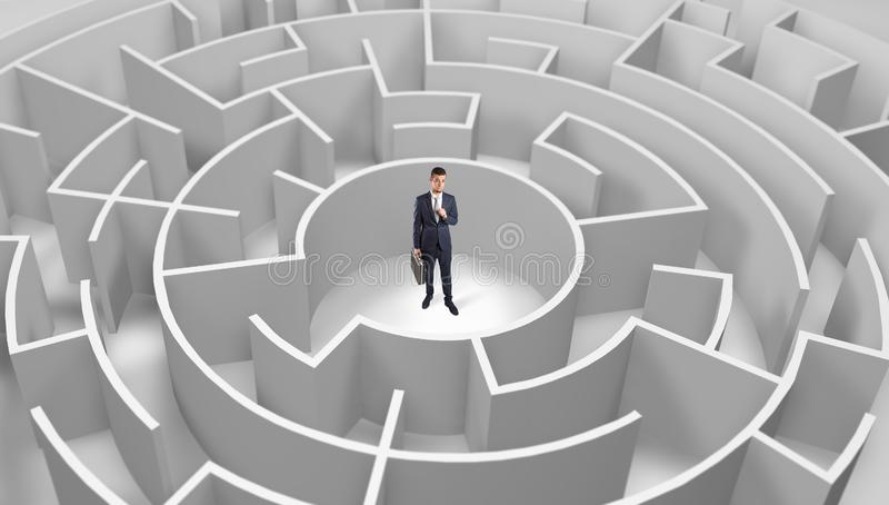 Position d'homme d'affaires ? un milieu d'un labyrinthe rond photos libres de droits